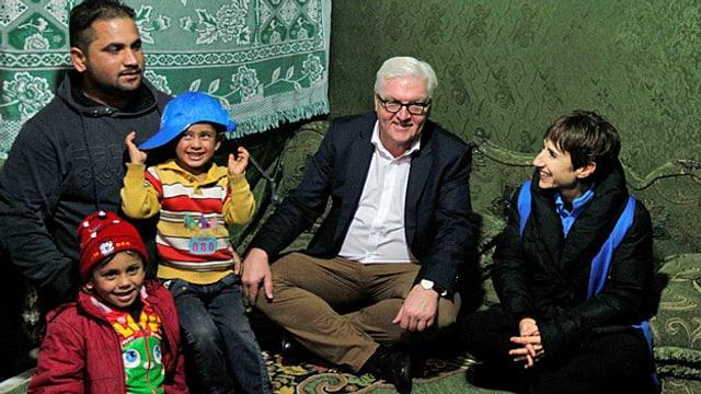 Frank Walter Steinmeier im Schneidersitz zusammen mit syrischen Flüchtlingen.