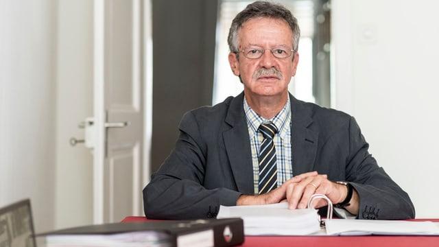 Strafrechtsprofessor Martin Killias sitzt vor einem Ordner mit Unterlagen.