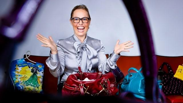 Rosanna Pierantognetti sitzt auf einem Sofa inmitten von Handtaschen.