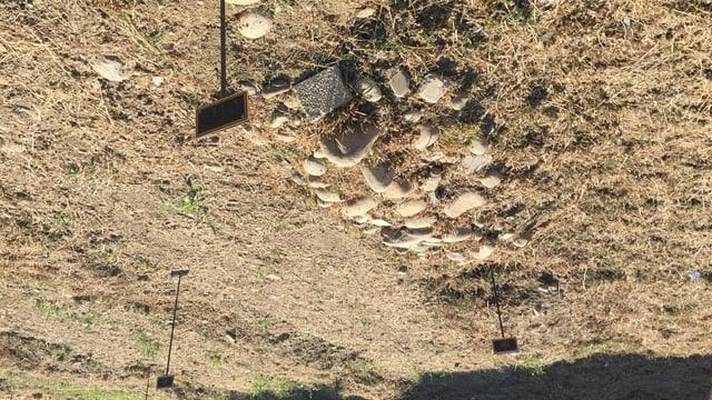 Mit Steinen aufgeschüttetes Grab, am einen Ende steckt ein Metallstab mit einem kleinen Schild.