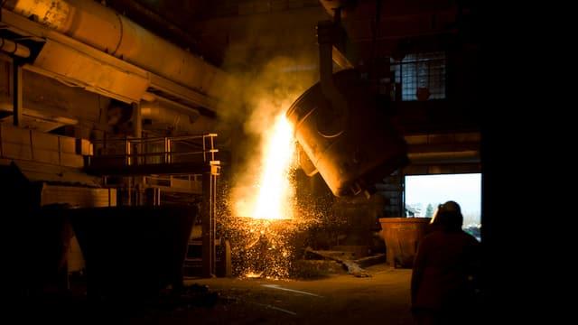Flüssiger Stahl fliesst aus einer Stahlpfanne.