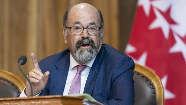 Politiker mit Brille, Veston und Krawatte am Rednerpult im Parlament.