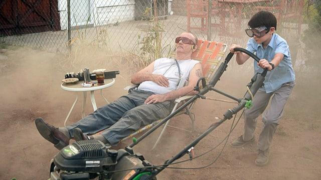 Bill Murray liegt im Liegestuhle, während der Junge Rasen mäht.