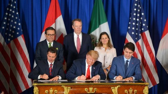 Unterzeichnung eines Abkommens, sechs Personen, Fahnen im Hintergrund