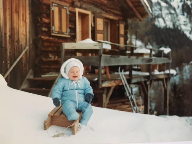 Priska sitzt auf einem Holzschlitten im Schnee.