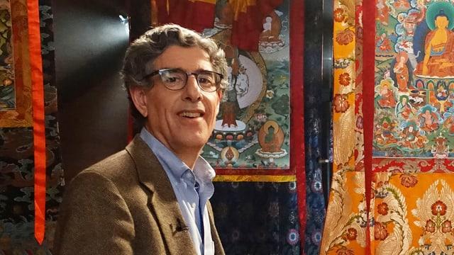 Mann mit Brille vor bunten Wandteppichen