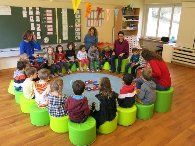 Kindergartenkinder sitzen in einem Kreis