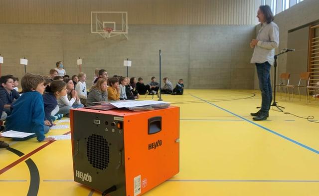 Orange Kiste, Luftreiniger, in einer Turnhalle. Im Hintergrund spricht ein Musiker zu einer Gruppe Kindern.