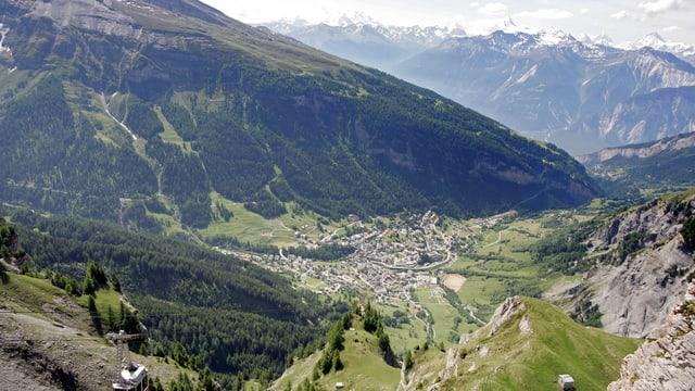 Blick auf Bergdorf, unten links Teil einer Seilbahn