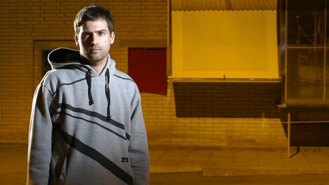 Manuel Oberholzer steht in mit einem grauen Kapuzenpulli in einer leeren Fabrikhalle.