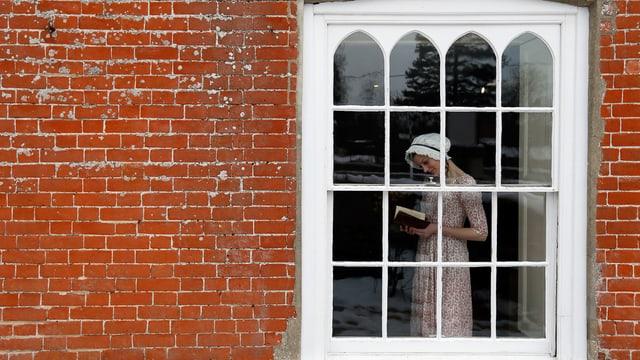 Rotes Backsteinhaus, Fenster, junge Frau in Garderobe des frühen 19. Jahrhunderts.