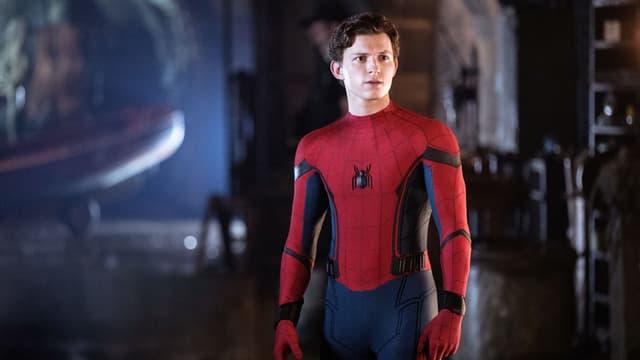 Ein Junge in einem engen Anzug mit einer abgebildeten Spinne auf der Brust steht in einem dunklen Raum.