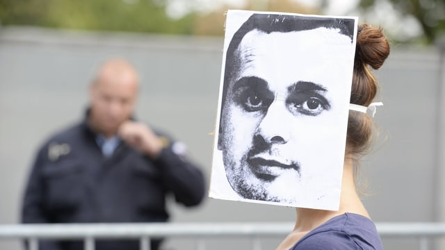 Eine Frau trägt ein grosses Foto eines Männergesichtes wie eine Maske um ihren Kopf gebunden.