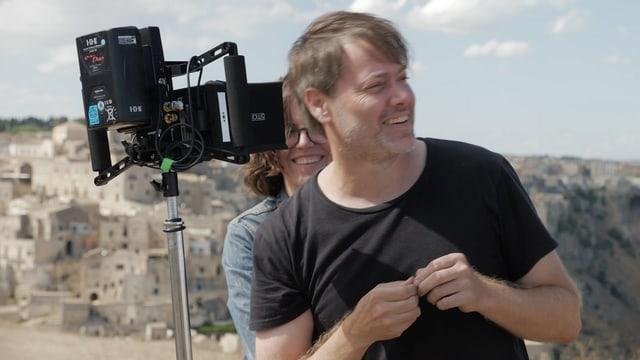 Mann mit kürzeren, braunen Haaren steht neben einem filmtechnischen Gerät. Hinter ihm ist die Stadt Matera zu sehen.