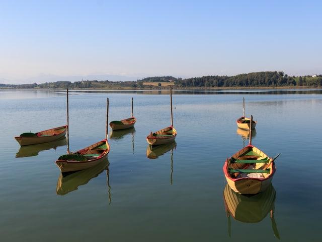 Stehende Boote auf dem spiegelglatten See.