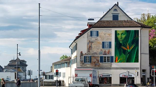 Ein grünes Bild mit einem Frauenkopf, projiziert auf das Zürcher Heimatwerk.