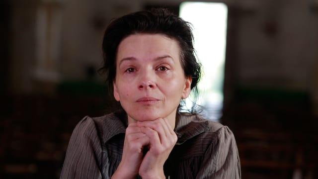 Die Schauspielerin Juliette Binoche blickt in die Kamera, das Gesicht auf die Hände gestützt.