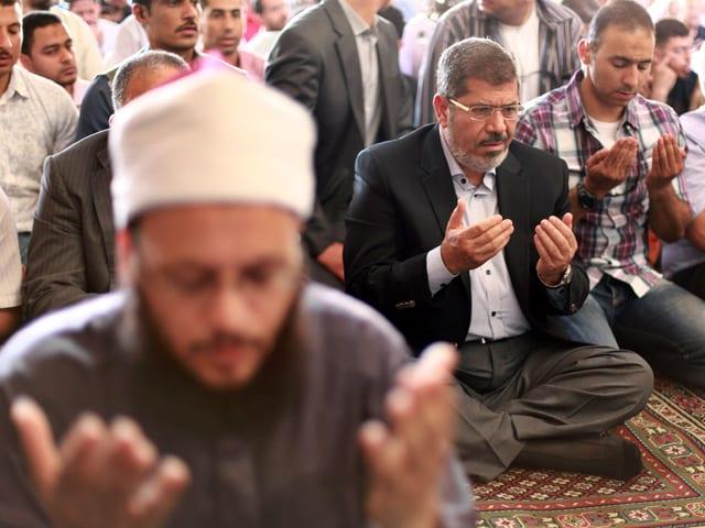 Mursi und weiter Gläubige sitzen auf dem Boden und beten