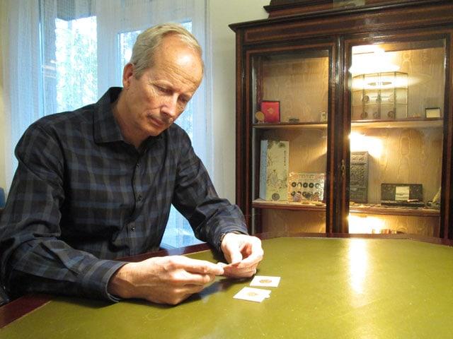Mann sitzt an einem Tisch und betrachtet Goldmünzen.