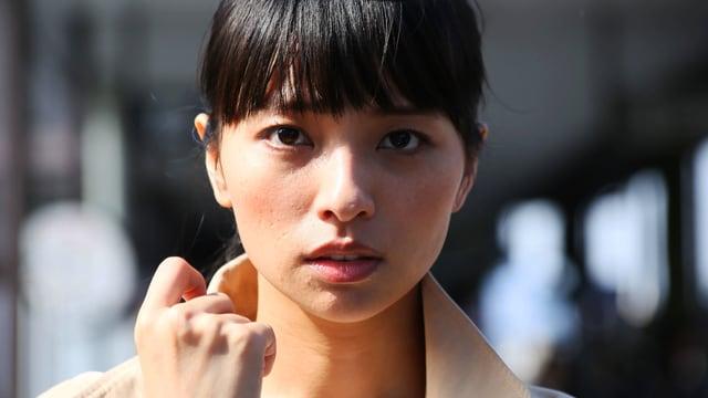 Nahaufnahme einer asiatisch aussehende Frau, die direkt in die Kamera blickt.