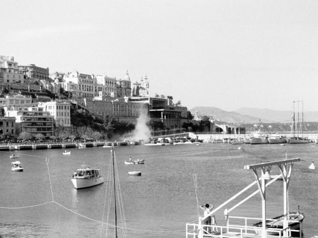 Alberto Ascari landet nach einem Unfall im Hafenbecken. Eine Staubwolke zeigt die Stelle, an der er ins Wasser stürzt.
