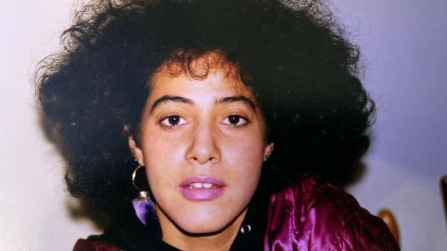 Altes Foto einer jungen Frau mit lockigen, schwarzen Haaren