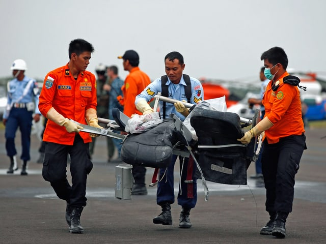Rettungskräfte mit Wrackteil