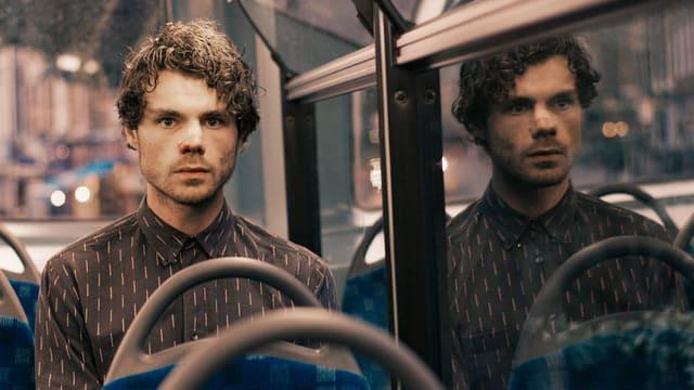 Ein Mann sitzt im Bus. Er hat ein Pflaster auf der Nase.