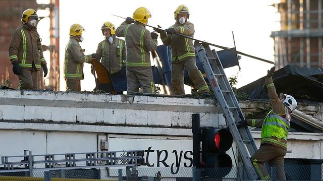 Bergungskräfte versuchen den Helikopter vom Dach des Pubs zu entfernen.