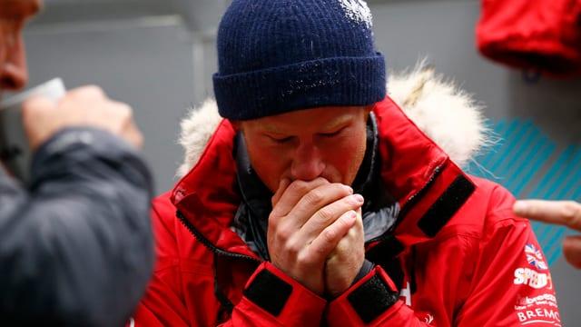 Prince Harry mit Wintermütze wärmt sich mit seinem Mund die Hände.