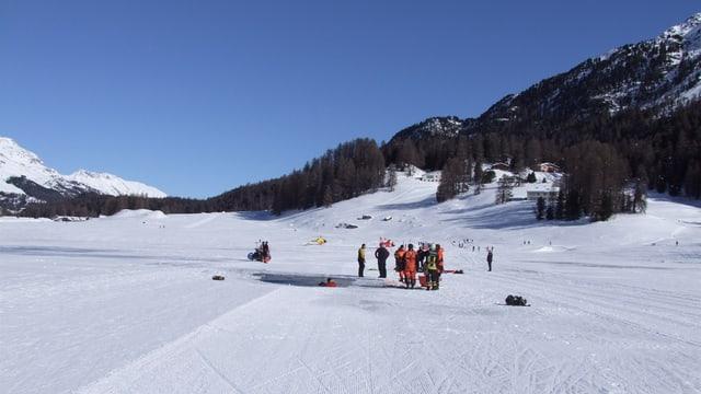 Eine Gruppe Menschen betrachtet ein Loch in der Eisdecke eines Sees.