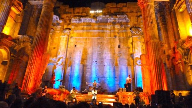 Eine Band spielt in einem antiken Tempel, der farbig beleuchtet ist.