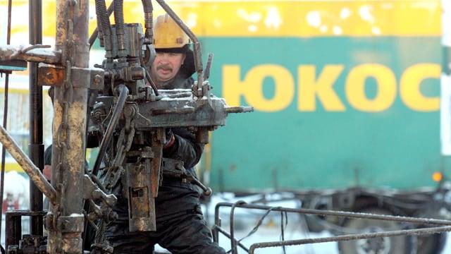 Ein Mann vor dem Logo Yukos