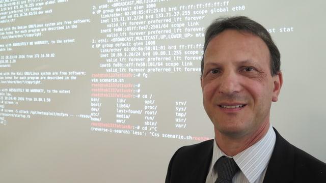 Er steht vor einer Wand mit Codes zur Abwehr von Cyber-Kriminellen.