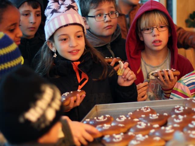 Kinder greifen nach den Lebkuchen.