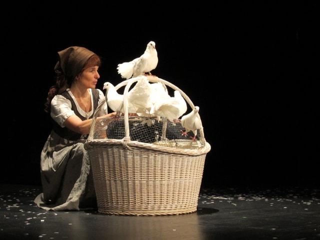 Aschenputtel mit einem Korb und echten weissen Tauben auf der Bühne.