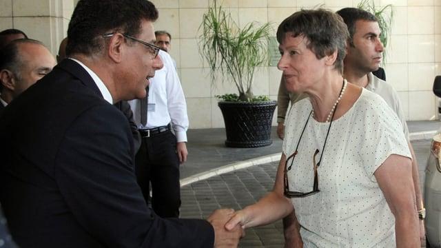 Ein Mann im Anzug schüttelt der deutschen Wissenschaftlerin die Hand bei der Ankunft.