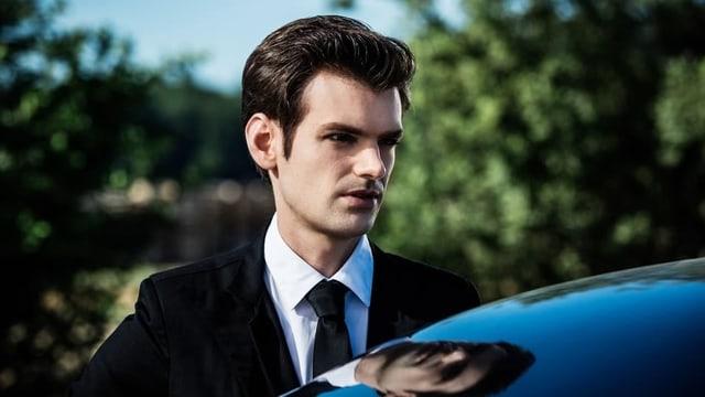 Ein Mann steht hinter einem Auto. Man sieht nur Kopf und Schultern. Er schaut ernst.
