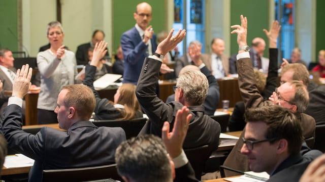 Männer und zwei Frauen in einem Ratssaal beim Abstimmen mit Hand erheben.