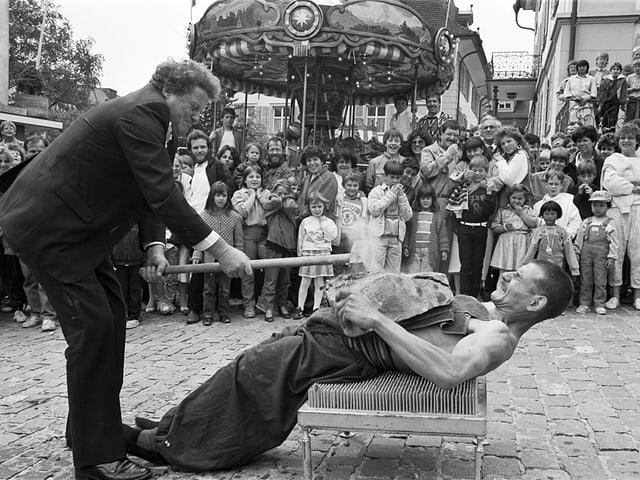 Ein Mann liegt auf einem Nagelbrett.