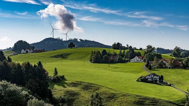 Wiesen und Hügel im Appenzellerland. Im Hintegrund zwei grosse Windräder.
