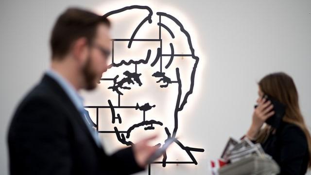 Kunstwerk eines Merkelkopfes, davor ein Mann und eine Frau, die die Art Düsseldorf besuchen.