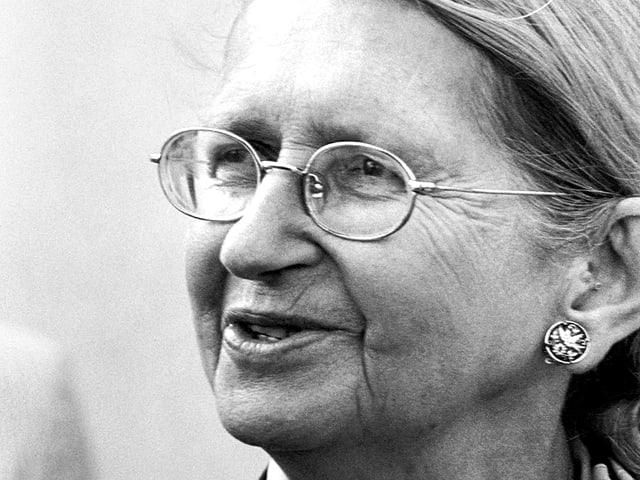 Porträt einer zur Seite blickenden Frau mit zurückgekämmten Haaren und Brille.