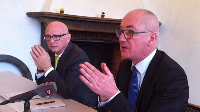 Isaac Reber und Renato Rossi mit der gleichen Geste hinter einem SRF-Mikrophon