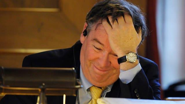 Stadtrat Martin Vollenwyder fasst sich lächelnd mit der Hand an den Kopf.