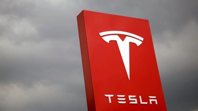 Das Tesla-Logo vor grauen Wolken