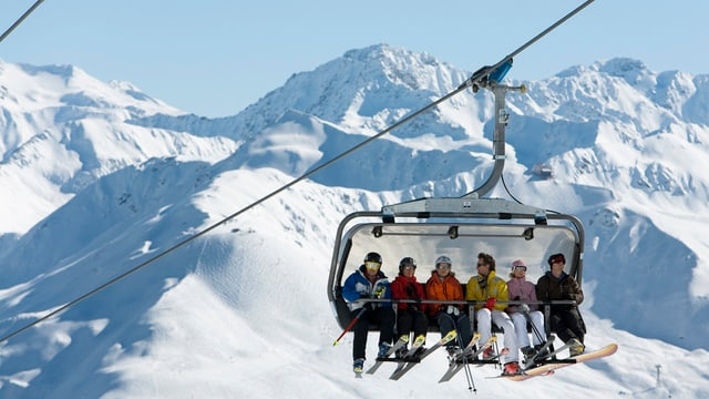 6 Skifahrer sitzen auf dem Sessellift Parsenn, im Hintergrund weisse Berge