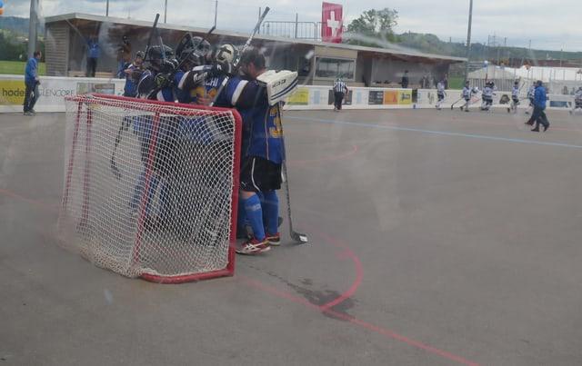 Streethockeyspieler jubeln mit Torwart