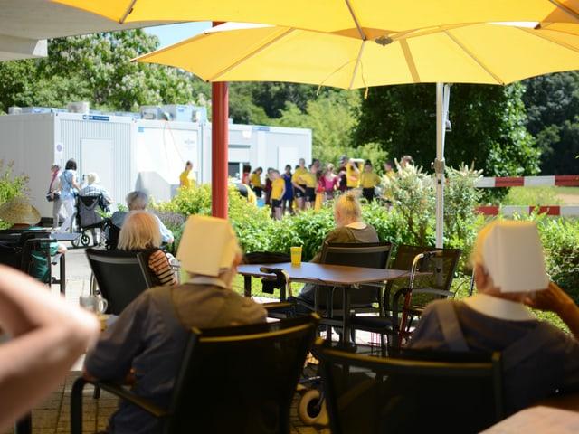 Im Schatten der Sonnenschirme warten betagte Nonnen auf den Auftritt der Jugendlichen.