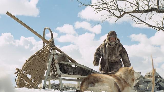 Ein Inuit mit einem Schlitten und ein Hund im Vordergrund.